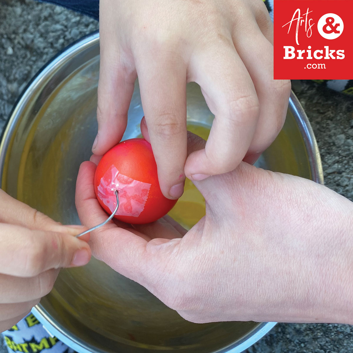 Use a paper clip to break up the yolk in prep for blowing out your easter egg.